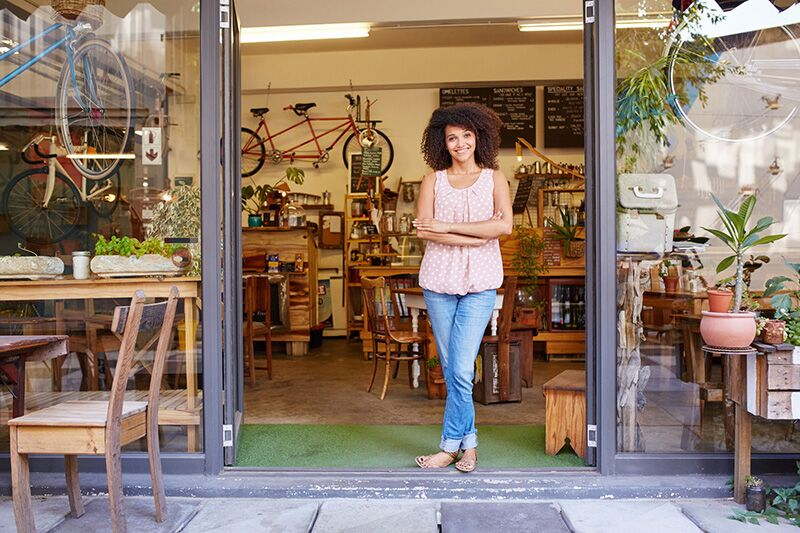 small business owner standing in front of her shop